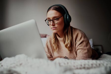 Young woman with glasses wearing headphones on an online video call at home during isolation - young female student attending online classes lectures - listening to music