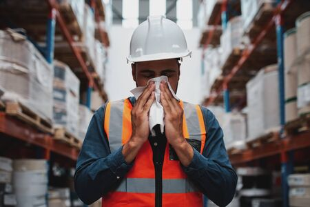 Warehouse manager coughing and sneezing while feeling sick and covering mouth with handkerchief