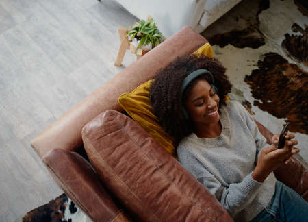 High angle view of woman lying on couch and listening to music using and typing message mobile phone in living room at home