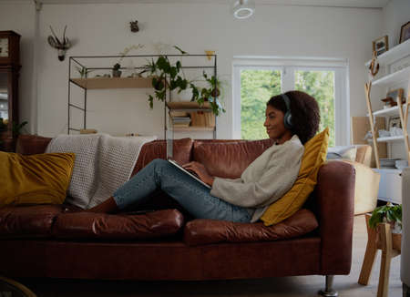 Side view of young woman relaxing at home watching webinar and typing with headphones sitting on couch