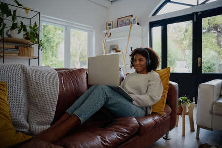 Woman sitting on couch using laptop watching video with headphones at home