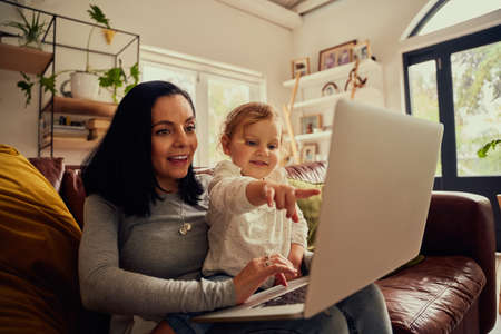 Little toddler girl sitting on mother lap using laptop on couch and pointing on screen showing something
