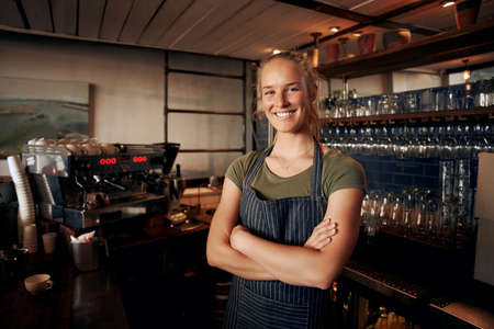 Portrait of young female waitress wearing apron standing behind counter in cafe with crossed hands