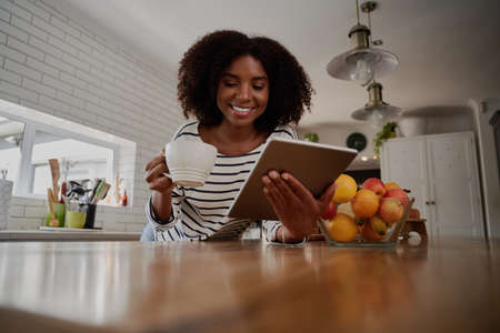 Smiling african woman standing in kitchen leaning on counter using digital tablet while drinking coffee 免版税图像