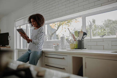 Young african woman standing in modern kitchen using digital tablet