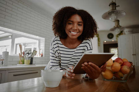 Portrait of young african woman browsing internet on digital tablet for new recipes in modern kitchen near bowl of fresh fruits