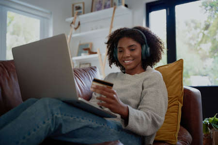 Happy woman listening to music with bluetooth headphones making online transaction using debit card and laptop Фото со стока