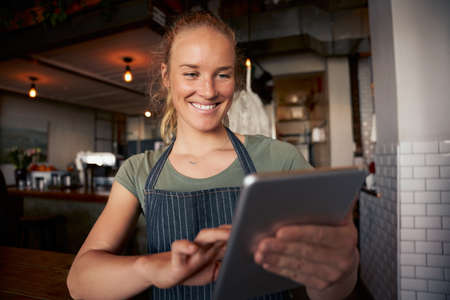 Happy female waitress in cafe wearing apron using digital tablet to check online orders