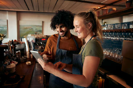 Cheerful male and female waiter wearing apron using digital tablet standing behind counter in cafe