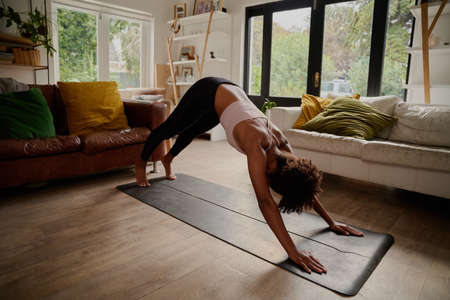 Sporty woman practicing yoga doing standing in downward facing dog exercise called adho mukha shavasana pose Stock Photo