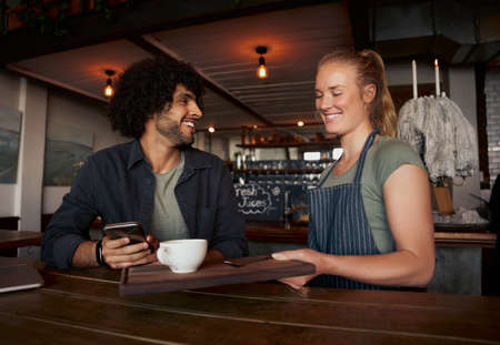 Cheerful female waitress serving coffee to young male customer with curly hair using smartphone in modern cafe