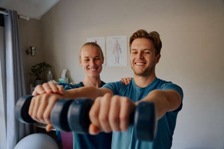 Smiling young female physiotherapist helping male patient do physical exercises to treat inflammation of the joints in arms