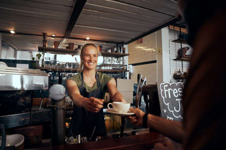 Beautiful young female waiter serving cup of coffee to customer in modern cafe