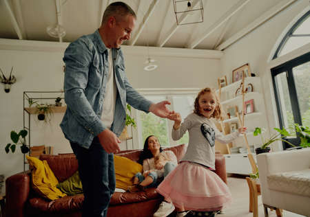 Handsome young father dancing with daughter at home while mother and sister sitting on couch watching