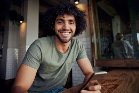 Portrait of handsome smiling man in sitting in cafeteria holding phone looking at camera