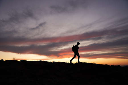 Silhouette of traveller with a backpack climbing up the mountain against beautiful horizon