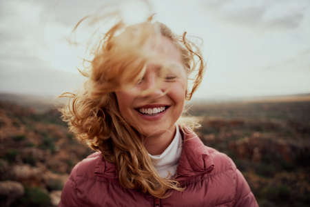 Portrait of young smiling woman face partially covered with flying hair in windy day standing at mountain - carefree woman Zdjęcie Seryjne