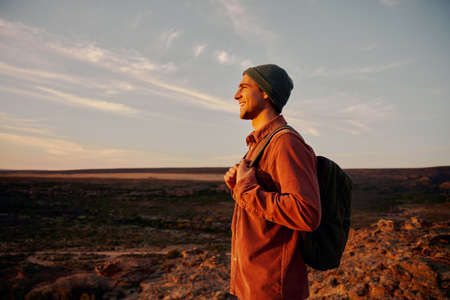 Happy hiker holding backpack looking at morning sunrise after successfully reaching mountain top Zdjęcie Seryjne