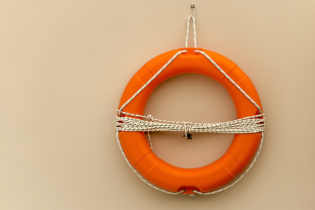 Orange life buoy with nautical ropes hanging on the wall photo