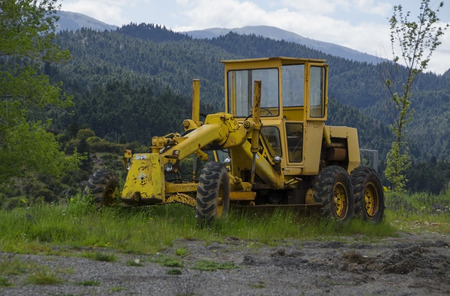 Old snow grungy grader on mountains photo