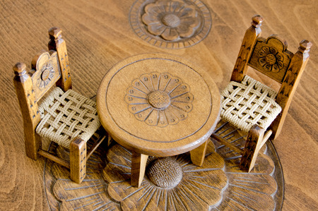 Mini wooden hand made chairs and table on carved table photo