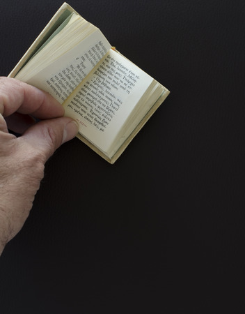 Old mans hand and mini book in greek language ,on  a leather notepad