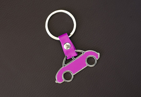 Key chain pink car on black leather pad photo