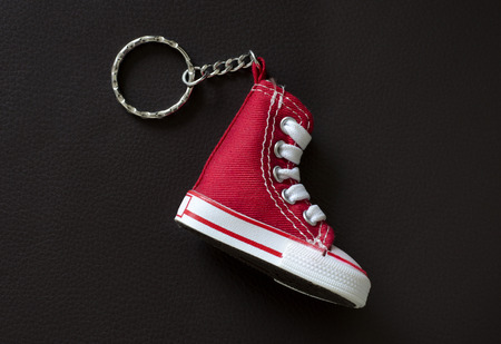 mini purse: Key chain with mini red  basketball shoe on black leather pad Stock Photo