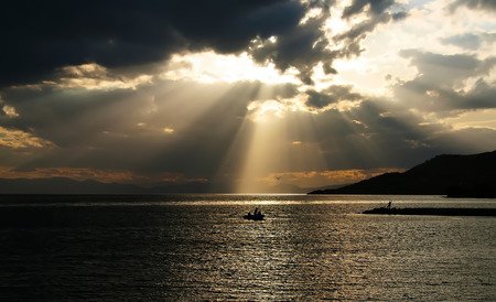 Fishermen after a storm under a dramatic sky with sunbeams above them photo