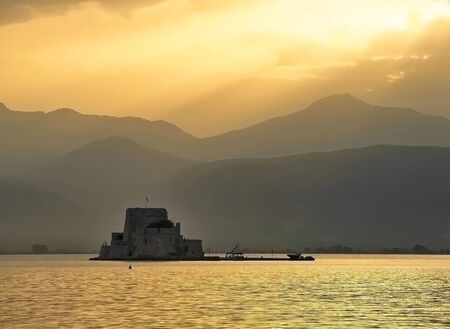 nauplio: Golden waters  surrounding distant fortress of Bourtzi near Nafplio, Greece