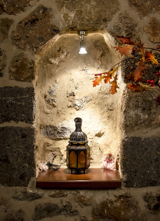 lamp made of stone: Warm Lighting Corner Decorated with a Beautiful Handmade Oriental lamp candle  and maple leaves on stone wall