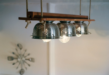 Warm lighting coming out from beautiful diy with kitchen equipment, lamps,ropes and wood hanged  from the ceiling