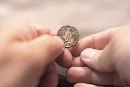asian coins: Close up capture of an Caucasian man hands holding and old greek new years cake coin showing king face