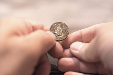 old coins: Primo piano cattura di un caucasico uomo mani detenzione e greco antico nuovi anni torta moneta mostrando re faccia