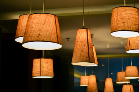 floor lamp: Warm lighting coming out from beautiful lamps on ceiling , while taking a hot cup of coffee in a trendy cafe with nice environment