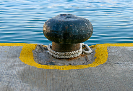 Old Rusty Iron Mooring Bollard and Nuatical Ropes. Yellow Painted Lines at the Dock