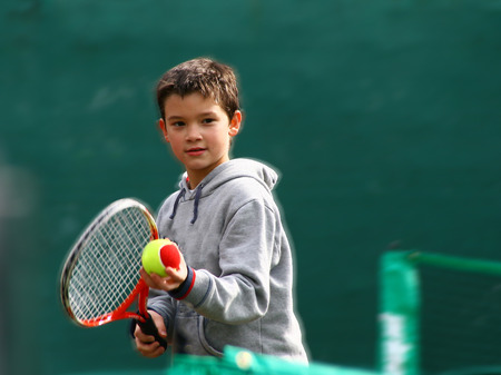 Little tennis player on a blurred green backround Stockfoto