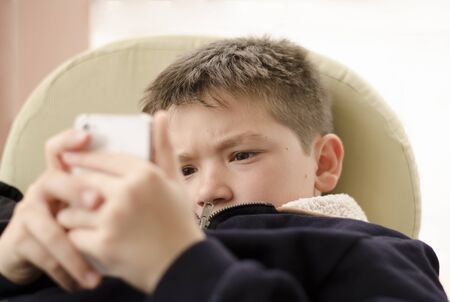 playful behaviour: Boy kid child playing with mobile phone