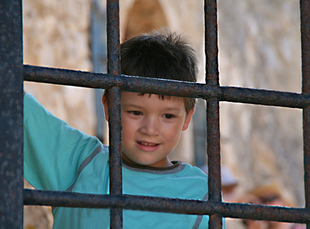 looking behind: Happy boy standing and looking  behind an old iron gate on greek castle