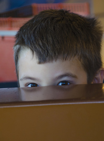 low self esteem: Little boy behind table at school