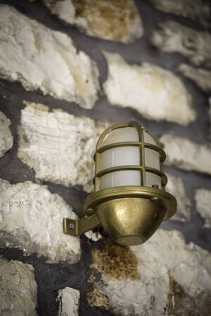 lamp made of stone: Retro classic style street electric iron bronze lamp over stone made wall