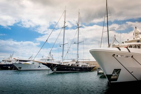 super yacht: Yacht Club with luxury yachts and motor boats under a dramatic cloudscape at the marina Zeas near Piraeus Port. Greece Stock Photo