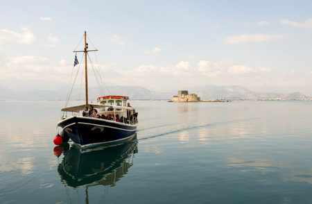 Nafplio,Bourtzi, Greece - December 27, 2015: Boats with tourists,sailing in calm waters of the Argolic Gulf, Greece. Sunrays reflect through blue green sea water.In the background the historic small island named Bourtzi, an old castle with prisons