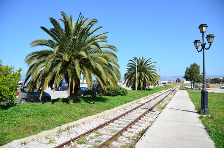 nauplio: Palm trees across old railway station platform and iron switch near Nafplio city,Peloponnese ,Greece