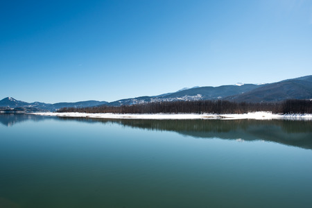Tranquil scenery. Landscape, Black snowy mountain, clear sky on lake at a winter day, Greece