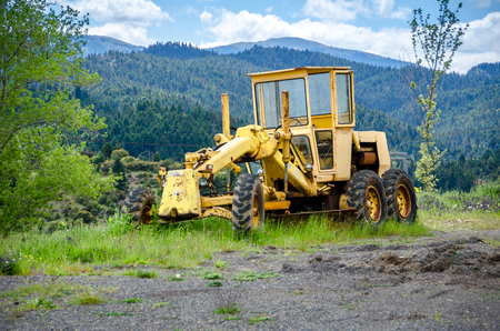 Old grader on mountainous road construction