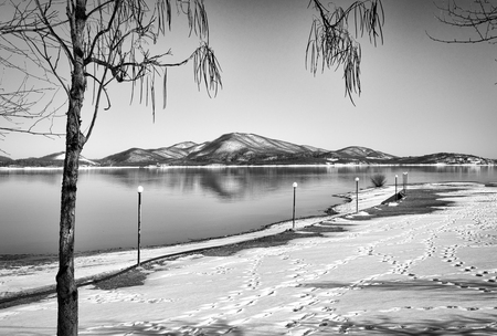 sweden resting: Tranquil wintry scenery. Landscape, Black snowy mountain, clear sky on lake at a winter day, Greece