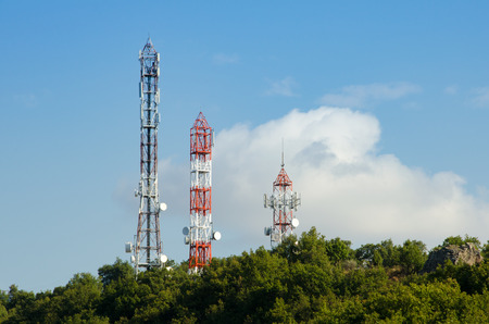 Three Telecommunication (GSM) towers with TV antennas ,satellite dishes  and repeaters at the top of a hill on a blue sky and a cloud on background