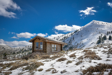 Winter snowy landscape with cabin hut amd blue sky and clouds on mountain Helmos near Kalavryta town in Greece