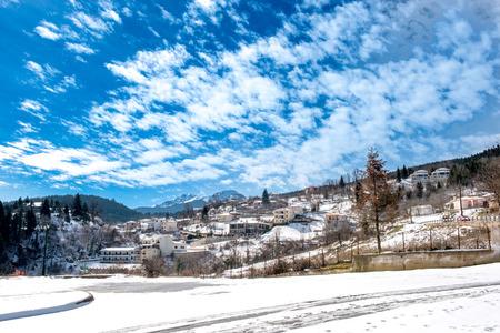 mountainous: Mountainous snowy village under cloudscape on Plastira lake in central Greece